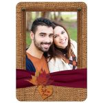 Fall in Love photo template wedding invites with a burgundy wine ribbon, orange painted wooden heart, and burnt orange, gold, yellow, rust, and red autumn maple leaves on it.