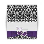 Great purple, black, and white damask pattern folded tented wedding reception place card with ribbon, bow and jewelled joined glitter hearts on it.