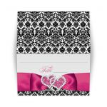 Pink, black, and white damask pattern wedding place card or escort cards with ribbon, bow, scroll, and jeweled joined hearts buckle brooch.