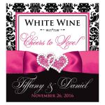 Personalized hot pink, black, and white damask pattern wedding wine bottle, water bottle or beverage labels with ribbon, bow, and jeweled joined hearts buckle brooch.