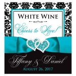 "Personalized ""Cheers to Love!"" turquoise, black, and white damask pattern wedding wine or beverage bottle label or sticker with aqua or teal blue ribbon, bow, and double jeweled joined hearts buckle brooch."
