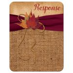 Rustic burlap wedding response enclosure cards with a wine colored ribbon, a gold tone twine bow, and burnt orange, rust, and red autumn leaves on it.