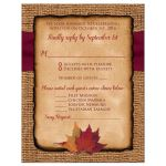 Burlap wedding enclosure card inserts with a wine colored ribbon, a gold tone twine bow, and burnt orange, rust, and red autumn leaves on it.