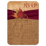 Small rustic burlap wedding response enclosure card with a burgundy colored ribbon, a golden tone twine bow, and burnt orange, red, and rust autumn leaves on it.
