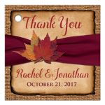 Personalized rustic burlap wedding favor tag with a burgundy colored ribbon, a twine bow, and burnt orange, red, yellow, and rust autumn leaves on it.