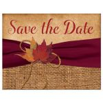 Rustic brown burlap wedding save the date post card with a burgundy wine colored ribbon, a gold tone twine bow, and burnt orange, red, and rust autumn leaves on it.