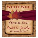 Rustic burlap wedding wine label, beverage label, bottle label or wedding favor sticker with a wine colored ribbon, a twine bow, and burnt orange, red, and rust autumn leaves on it.