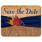 ​Rustic brown burlap photo template wedding save the date postcard with a navy blue colored ribbon, a twine bow, and burnt orange, red, and rust autumn leaves on it.