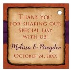 ​Personalized rustic autumn wedding favor tag in fall colors of burnt orange, gold, rust, red and brown with dried maple leaves, a printed twine bow and dark aubergine purple printed ribbon on an orange suede look background.