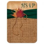 ​Rustic burlap wedding response enclosure card insert with a hunter green ribbon, a golden twine bow, and burnt orange, red and rust autumn leaves on it.