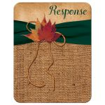 Rustic burlap wedding response enclosure card insert with meal selections and a hunter green ribbon, a golden twine bow, and burnt orange, red and rust autumn leaves on it.