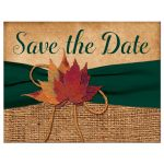 Rustic burlap wedding save the date postcard with a hunter green ribbon, a golden twine bow, and burnt orange, red and rust autumn leaves on it.