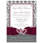 Burgundy wine, charcoal grey and white damask pattern wedding invitation with ribbon, bow, glitter and a jeweled joined hearts buckle on it.