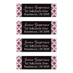 ​Pink, black, and white return address mailing labels with the French fleur-de-lis pattern on them.