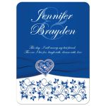 ​Royal blue and white floral wedding invitation with silver heart brooch, ribbon, flowers, and ornate scrolls.