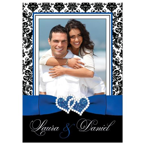 Great royal blue, black, and white damask photo wedding invitation with ribbon, glitter and a jeweled joined hearts buckle brooch on it.