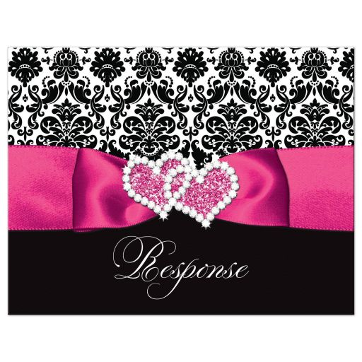 Hot pink, black, and white damask pattern wedding response reply rsvp postcard with ribbon, bow, scroll, and jeweled joined hearts buckle brooch.