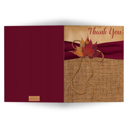 Affordable rustic burlap wedding thank you card with a burgundy ribbon, a golden twine bow, and burnt orange, red and rust autumn leaves on it.