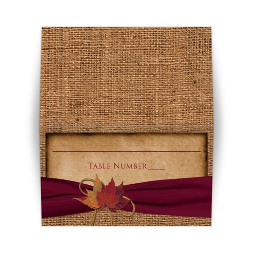 Rustic folded FAUX burlap wedding place card or escort card with a burgundy wine colored ribbon, a golden twine bow, and burnt orange, yellow, red, and rust autumn leaves on it.