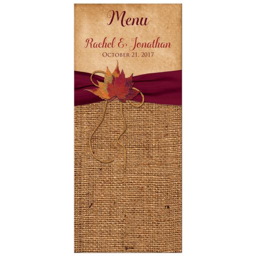 Rustic burlap wedding reception menu card with a burgundy wine ribbon, a gold tone twine bow, and burnt orange, red, brown, and rust autumn leaves on it.