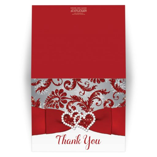 Winter wonderland wedding thank you card with a silver grey background overlaid with a red FAUX glitter damask pattern and white snowflakes with a PRINTED red ribbon and bow and pair of diamond jewels and FAUX glitter joined hearts brooch on it.