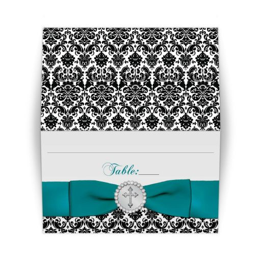 ​​Folded black and white damask pattern place card with a printed ribbon and bow with a round silver brooch surrounded by printed on diamond jewels with an ornate silver Christian Cross on it.
