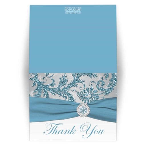 ​Winter wonderland wedding thank you card in ice blue, silver, and white snowflakes with ribbon and crystal buckle.