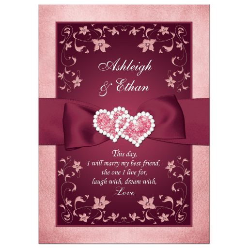 Burgundy wine, blush pink, rose gold and white floral wedding invitation with burgundy ribbon, bow, and glittery crystal jewels joined hearts buckle brooch with rose gold metallic border.