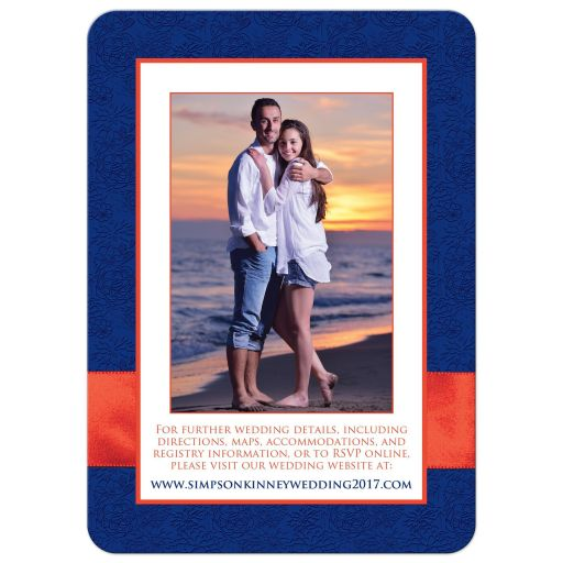 Navy blue, orange, and white floral wedding invites with ribbon, glitter and a pair of jeweled double joined hearts buckle brooch on it.