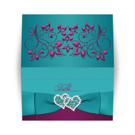 Folded plum purple, teal blue green and magenta pink floral wedding place card or escort cards with ribbon, bow, glitter, and jeweled joined hearts.