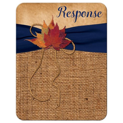 ​Rustic brown burlap wedding response enclosure card with a navy blue ribbon, a twine bow, and burnt orange, red and rust autumn leaves on it.