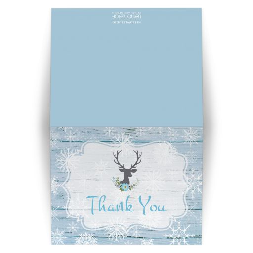 Rustic blue and white snowflakes winter wedding thank you card with blue flowers, gray deer head, grey lantern, and wood.