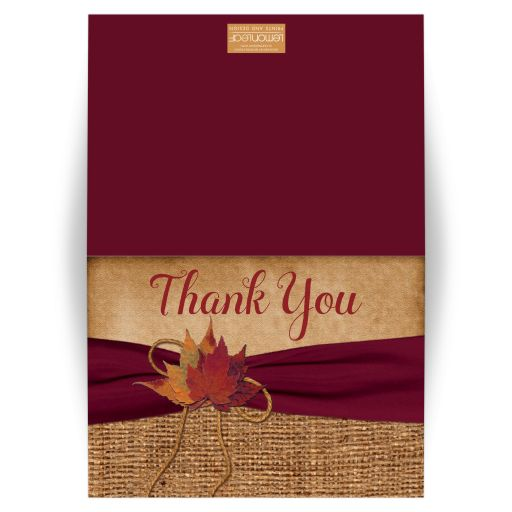 Rustic burlap photo template wedding thank you card with a burgundy wine ribbon, a golden twine bow, and burnt orange, red, and rust autumn leaves on it.