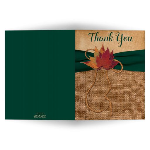 Rustic burlap wedding thank you card with a hunter green ribbon, a golden twine bow, and burnt orange, red, and rust autumn leaves on it.