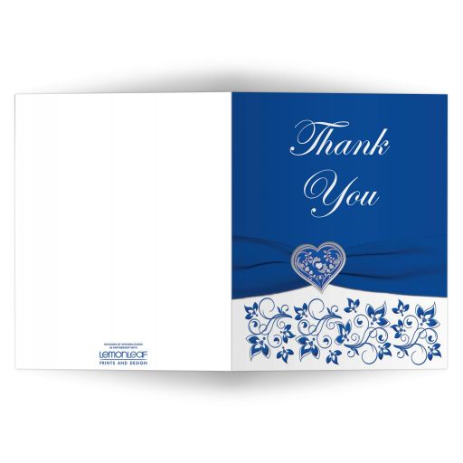 Personalized royal blue and white floral wedding thank you card with silver heart brooch, ribbon, flowers, ornate scrolls, and photo template.