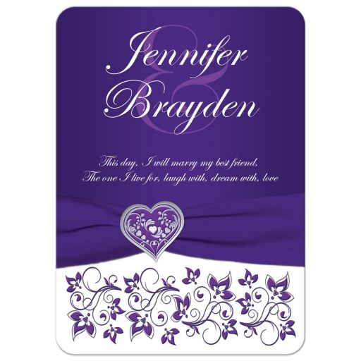 Purple ​and white floral wedding invitation with silver heart brooch, ribbon, flowers, and ornate scrolls.