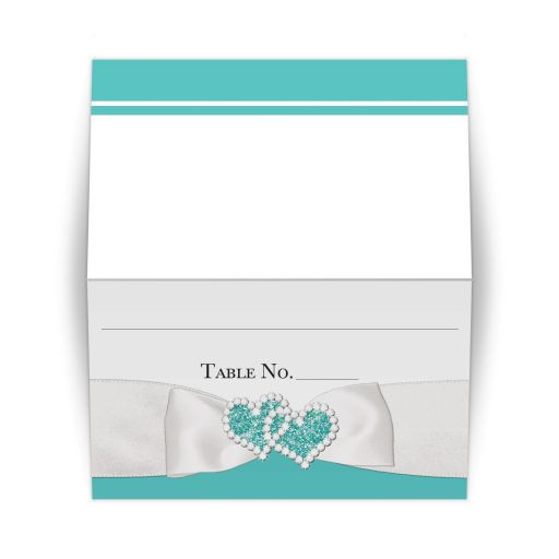 ​Tiffany blue and white folded place cards or escort cards with a white satin look ribbon and bow with joined jeweled hearts brooch with diamonds and glitter.