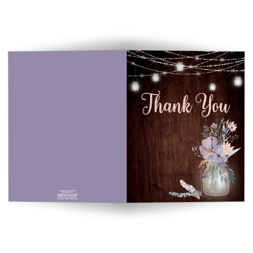 ​Rustic brown wood, mason jars, string lights and purple, pink, blue, peach and green flowers, foliage, and feathers wedding thank you note card for a barn or country wedding.
