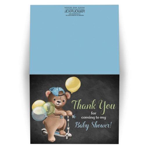 ​Cute chalkboard baby shower thank you card with brown bear wearing a denim ball cap while riding a scooter with blue, green, and yellow balloons and bunting.